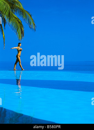 Woman balancing on edge of infinity pool, Maldives, Indian Ocean, Asia - Stock Photo