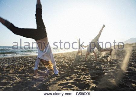 Friends doing cartwheels on beach - Stock Photo