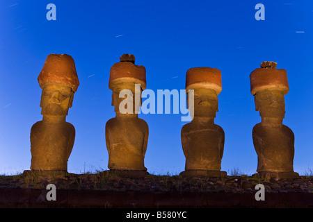 Anakena beach, monolithic giant stone Moai statues of Ahu Nau Nau, four of which have topknots, Rapa Nui, Chile - Stock Photo
