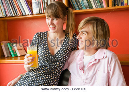Teenage couple laughing in cafe - Stock Photo