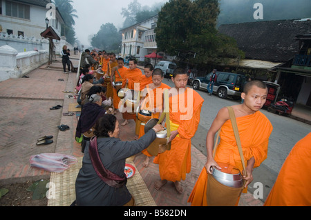 Buddhist monks collecting alms in the early morning, Luang Prabang, Laos, Indochina, Southeast Asia, Asia - Stock Photo