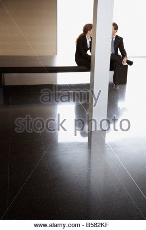 Businesspeople talking in office lobby - Stock Photo