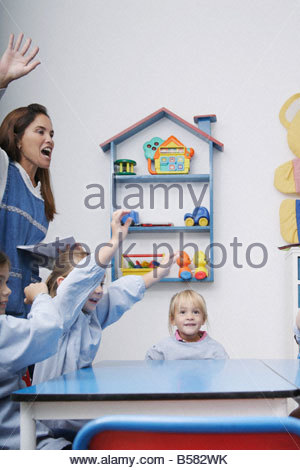 Teacher and students cheering in class - Stock Photo