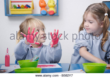 Girls finger-painting in classroom - Stock Photo