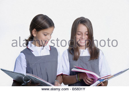 School girls looking at notebooks - Stock Photo