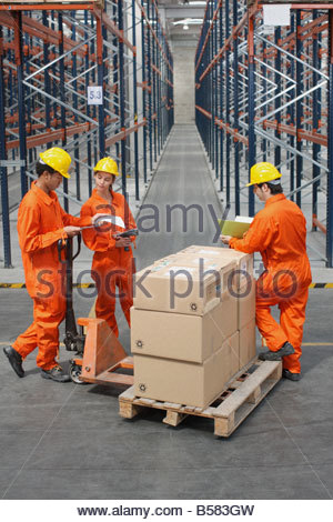 Workers loading boxes in warehouse - Stock Photo