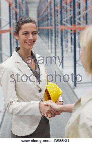 Businesswoman shaking hands in warehouse - Stock Photo