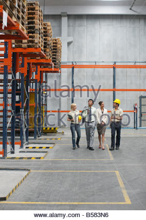 Businesspeople and workers in warehouse - Stock Photo