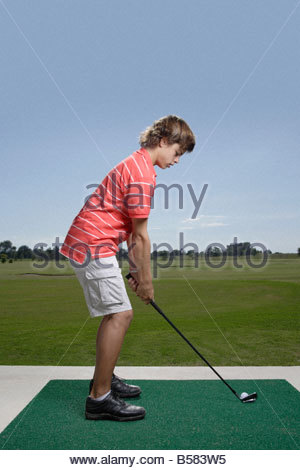 Boy golfing on driving range - Stock Photo