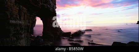 View over North Sea from beach at Marsden Bay, rock arch in Marsden Rock, South Shields, Tyne and Wear, England - Stock Photo