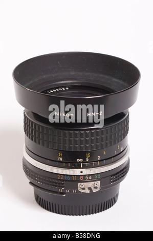 A Nikon 28mm f3.5 ai Nikkor wide angle manual focus lens with hn-2 lens hood attatched for Nikon 35mm slr film cameras