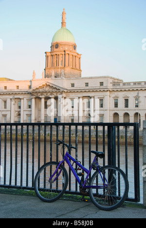 A bike locked on the rails looking over towards the Custom House in Dublin - Stock Photo
