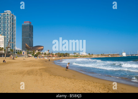 People at Platja de la Barceloneta beach in front of Port Olimpic in Barcelona Spain Europe - Stock Photo