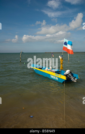 Small boat in South China Sea with flag and blue skies - Stock Photo