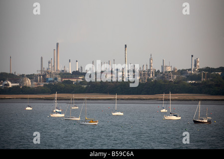 Fawley oil refinery and natural gas terminal and storage depot tanks near Hythe with sailing boats on Southampton - Stock Photo