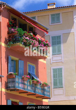 Balconies with blue wrought iron and shutters, pots of geraniums, Villefranche on the Cote d'Azur, Provence, France - Stock Photo