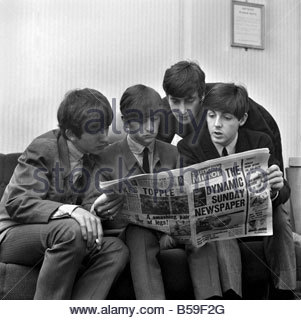 Beatles pop grouo reading the Sunday Mirror newspaper. ;Left to right: George Harrison, Ringo Starr, John Lennon - Stock Photo