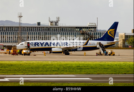 A Ryanair plane is boarded by passengers at Glasgow Prestwick International Airport, Ayrshire, Scotland. - Stock Photo