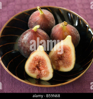 still life three whole figs and one sliced in a japanese bowel - Stock Photo
