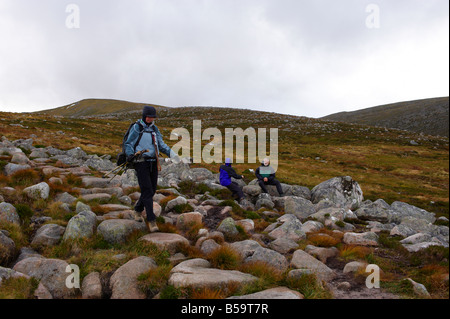 Lady walker walking down the path from Ben Macdui approaching Glenmore Forest car park Scotland UK - Stock Photo
