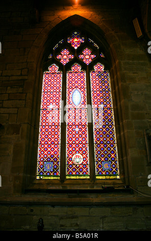 A gothic stained glass window in a 15th Century English Church - Stock Photo