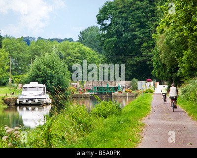 Cyclists on the towpath at a Lock on the Nantes Brest Canal at Cadoret, Morbihan, Brittany, France Europe - Stock Photo