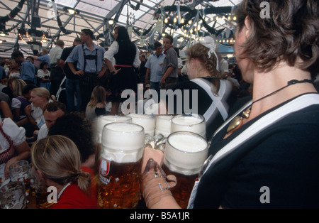 Oktoberfest Annual beer festival Huge hall Waitress woman carrying tray of huge steins beer jugs glasses MUNICH - Stock Photo