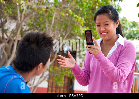 Teenage girl student takes photo or video clip on her mobile phone of a school friend in sunny school playground - Stock Photo