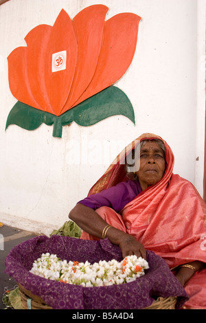 Women sell flowers in Mysore, India. A red lotus with an Om symbol on it is on the wall above here. - Stock Photo