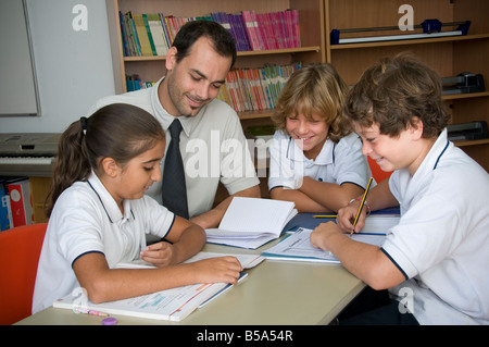 Small interactive study group of happy junior school pupils with male teacher in informal language lesson - Stock Photo