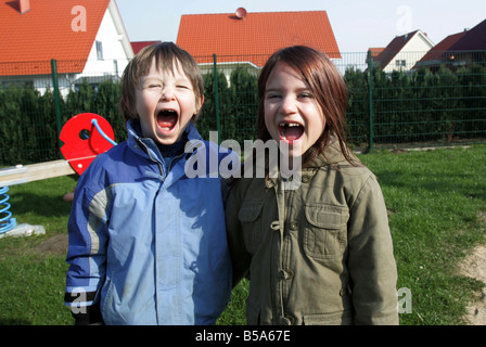 A boy and a girl screaming loudly - Stock Photo
