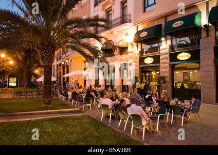 People sitting outside a busy bar on Plaza de la Reina in the historic El Carmen city centre of Valencia Spain - Stock Photo