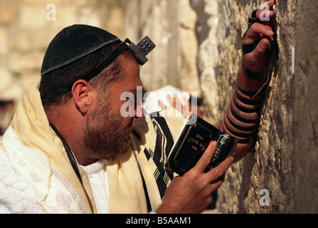 Close-up of Jew wearing shawl, skull cap and phylactery and holding a book, praying at the Western Wall in Jerusalem, - Stock Photo