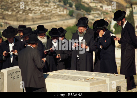 Orthodox Jews praying on a tomb on the Mount of Olives, in Jerusalem, Israel, Middle East - Stock Photo