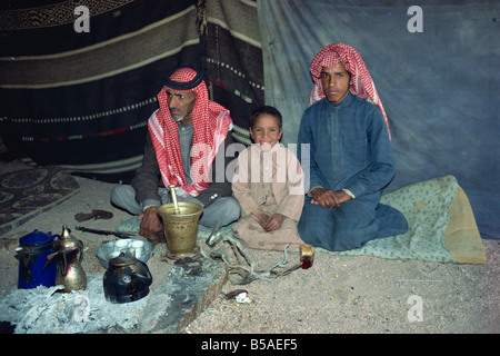 Portrait of three Bedouin sitting inside tent with tea or coffee pots and glasses in Wadi Rum Jordan Middle East - Stock Photo