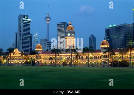 City skyline and the Sultan Abdul Samad Building illuminated at dusk seen from Merdaka Square Kuala Lumpur Malaysia - Stock Photo