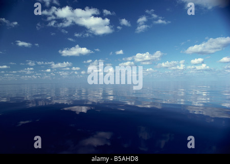 Reflections of white clouds and blue sky in the water of the Indian Ocean in the Maldives, Indian Ocean - Stock Photo