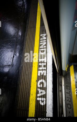 Mind the Gap sign seen through opened underground train door, London, England - Stock Photo