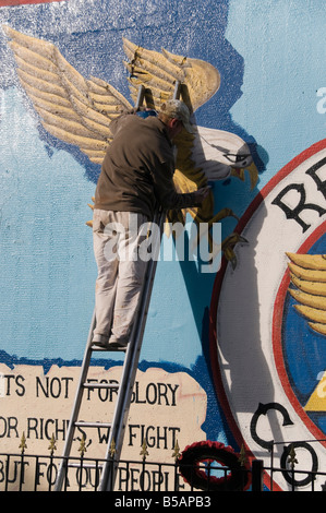 Man on ladder painting a protestant mural off the Shankill Road, Belfast - Stock Photo