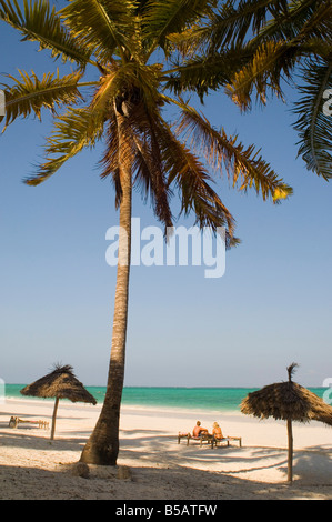 A couple sitting on traditional coconut wood sunbeds beneath palm trees Paje Beach Zanzibar Tanzania East Africa - Stock Photo