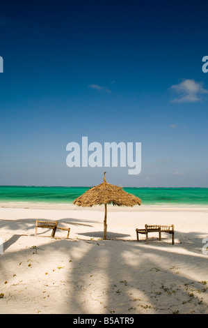 A thatched umbrella and traditional coconut wood sunbeds on Paje Beach Paje Zanzibar Tanzania East Africa Africa - Stock Photo