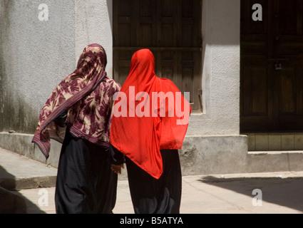 Women wearing colourful headscarves walking in Stone Town Zanzibar Tanzania East Africa Africa - Stock Photo