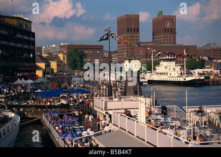 Open air restaurants around harbour, with the clock tower, and the Town Hall behind, Oslo, Norway, Scandinavia, - Stock Photo