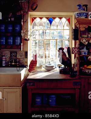 Gothic-style window with stained glass inserts above ceramic sink and worktop with cat and chicken ornaments in - Stock Photo