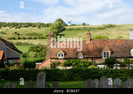 Country cottage in a village with a windmill on the hill in the background on a sunny day wide horizontal shot - Stock Photo