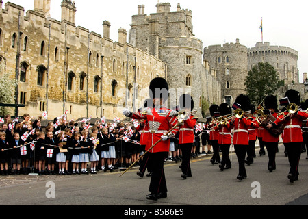 The military band of The Irish Guards marches past cheering school children waving flags of St George with Windsor - Stock Photo