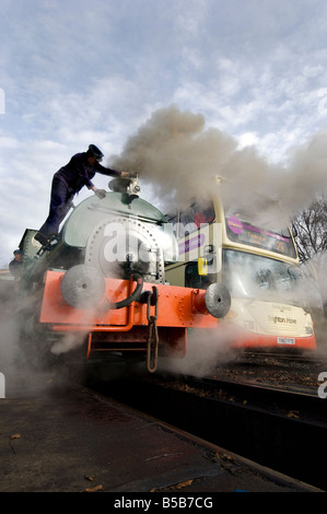 A saddletank steam locomotive with driver and fireman next to a double decker bus at Isfield station in Sussex - Stock Photo