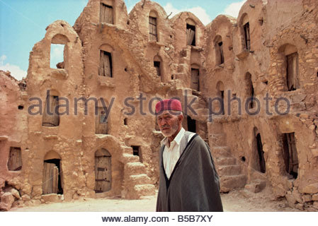 Ghorfas Ksar Ouled Soltane with man standing in foreground Tunisia Africa D Beatty - Stock Photo