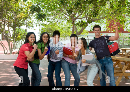 Group of happy attractive senior teenage school students with team spirit having fun outside on sunny school playground - Stock Photo