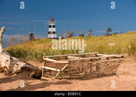 An abandoned lobster trap sits in front of the West Point Lighthouse on the beach on Prince Edward Island, Canada. - Stock Photo